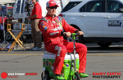 May 21, 2015; Concord, NC, USA; NASCAR Sprint Cup Series driver Kyle Busch (18) rides a motorized cooler to a press conference before qualifying for the Coca-Cola 600 at Charlotte Motor Speedway. Mandatory Credit: Randy Sartin-USA TODAY Sports